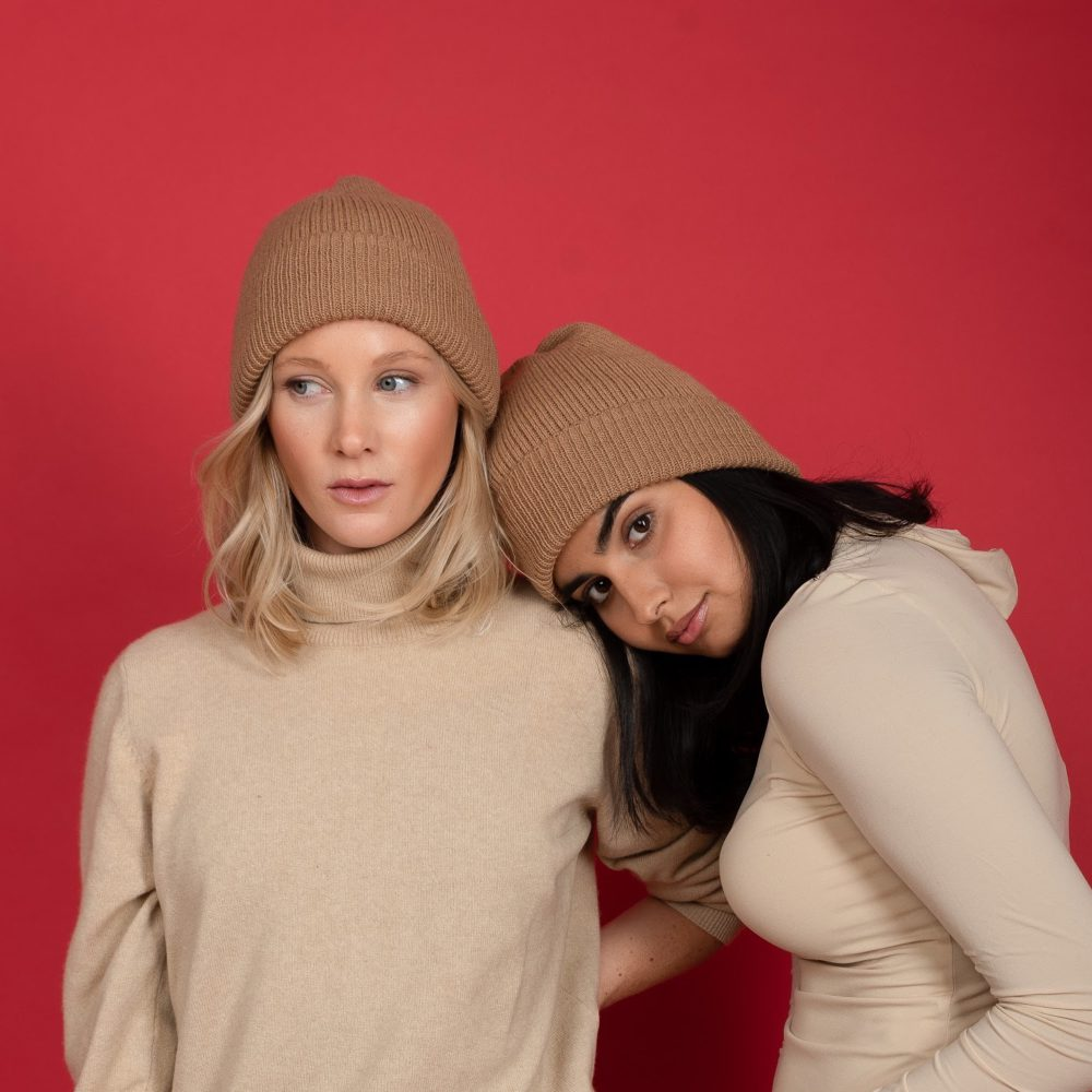 models styling a light brown baby alpaca wool beanie by washein